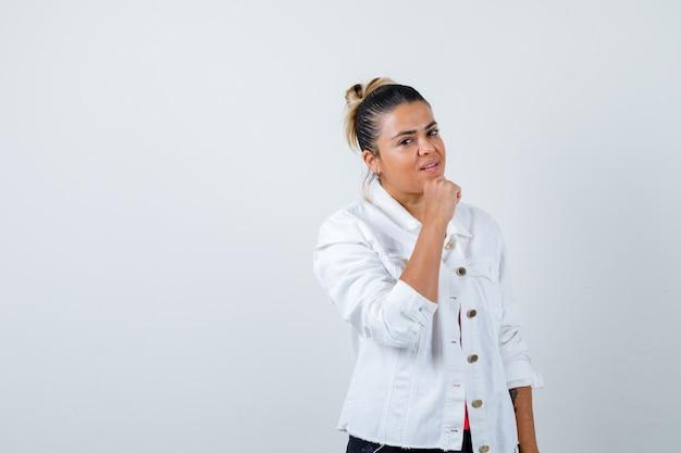 Jonge dame met vuist op kin in t-shirt, witte jas en zelfverzekerd, vooraanzicht.