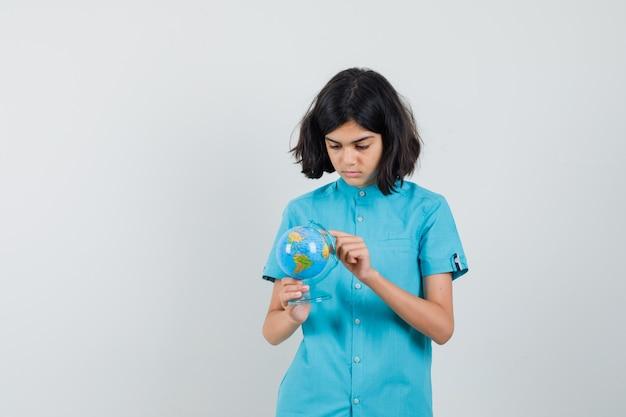 Jonge dame mini globe in blauw shirt houden en gericht kijken.