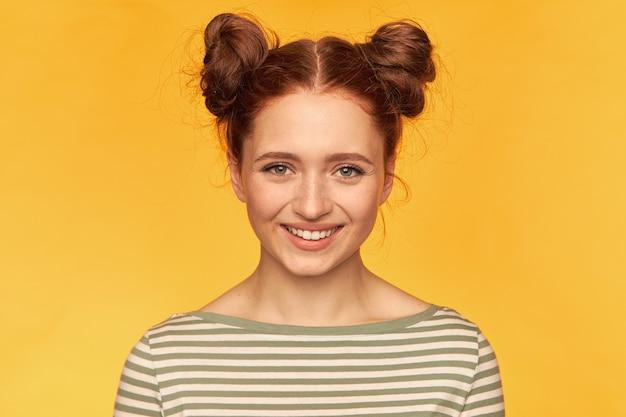 Jonge dame, mooie, charmante roodharige vrouw met twee broodjes en een gezonde huid. voelt geluk. gestreepte trui dragen en kijken geïsoleerd, close-up over gele muur