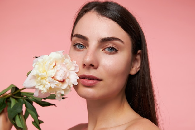 Jonge dame, mooie, charmante vrouw met lang donkerbruin haar en een gezonde huid, wang aanraken met een bloem. kijken, close-up, geïsoleerd over pastel roze muur