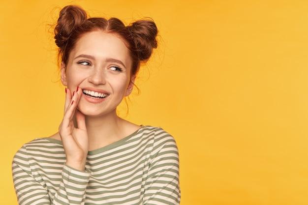 Jonge dame, mooie gembervrouw met twee broodjes en gezonde huid. glimlach en raak de mondhoek aan. gestreepte trui dragen en naar rechts kijken op kopie ruimte, close-up over gele muur