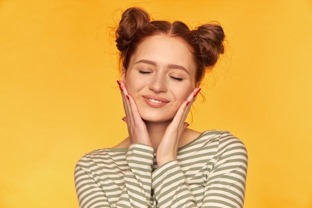Jonge dame, mooie, schattige roodharige vrouw met twee broodjes. ze draagt een gestreepte trui en streelt haar wangen. gezonde huid. warme en gelukkige gevoelens uiten. stand geïsoleerd, close-up over gele muur