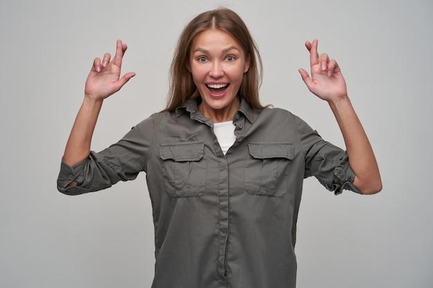 Jonge dame, mooie vrouw met bruin lang haar. het dragen van grijs shirt en kruiste haar vingers. vrolijk, een wens doen. glimlachend. kijken naar de camera geïsoleerd over grijze achtergrond