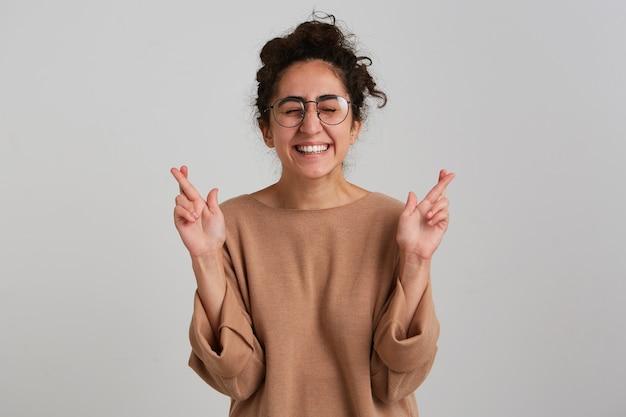 Jonge dame, mooie vrouw met donker krullend haarbroodje, beige trui en bril dragen
