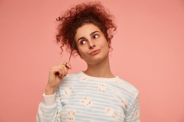 Jonge dame, mooie vrouw met gember krullend haar. gestreepte trui aan met konijntjes en speelt met haar krulletje. sta geïsoleerd over een pastelroze muur en kijk naar links in de kopieerruimte