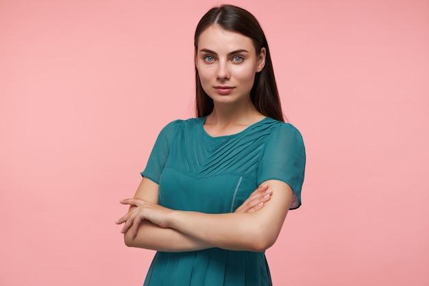 Jonge dame, mooie vrouw met lang donkerbruin haar. handen vouwen op een kist, handen kruisen en kijken geïsoleerd over pastelroze muur. smaragdgroene jurk dragen