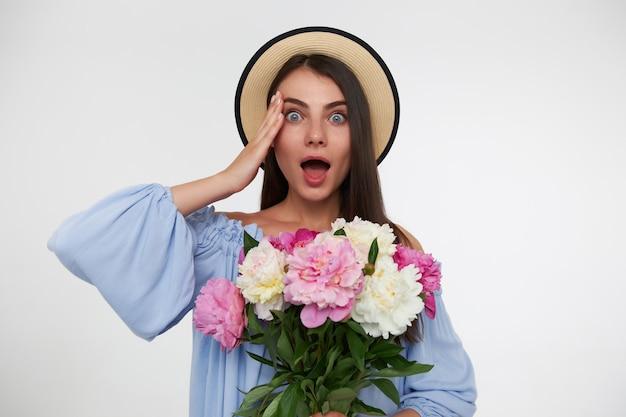 Jonge dame, mooie vrouw met lang donkerbruin haar. het dragen van een hoed en een blauwe jurk. boeket bloemen vasthoudend en geschokt haar hoofd aanraken. kijken geïsoleerd over witte muur