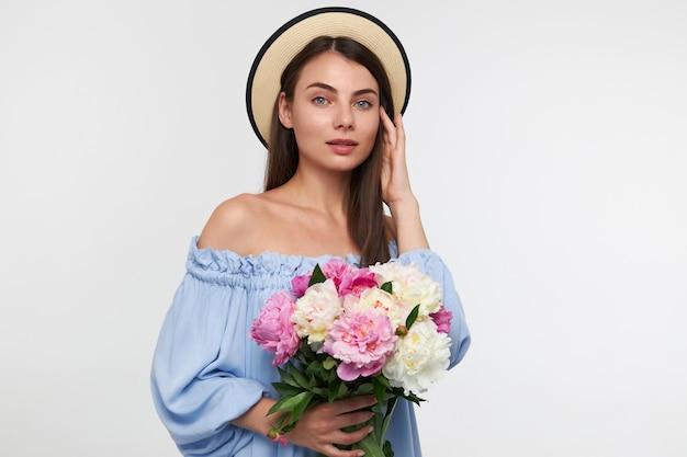 Jonge dame, mooie vrouw met lang donkerbruin haar. het dragen van een hoed en een blauwe mooie jurk. een boeket van prachtige bloemen vasthouden en haar aanraken. kijken geïsoleerd over witte muur