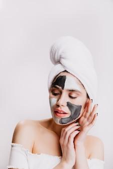Jonge dame na douche geniet van spa gezichtsprocedure. portret van vrouw in kleimasker op witte muur.