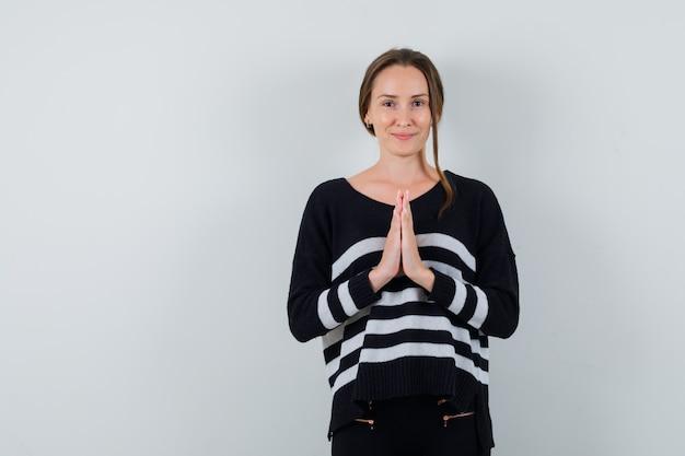 Jonge dame namaste gebaar in overhemd tonen en schattig op zoek