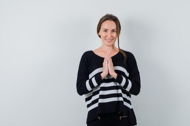 Jonge dame namaste gebaar in overhemd tonen en vrolijk kijken