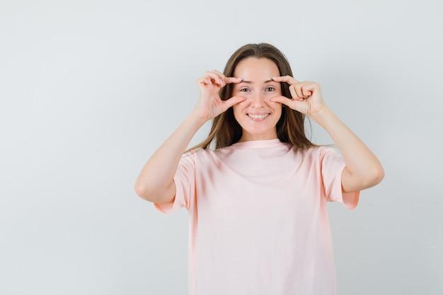 Jonge dame ogen openen met vingers in roze t-shirt en optimistisch op zoek