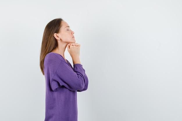 Jonge dame omklemde handen in biddend gebaar in violet overhemd en op zoek vredig. .