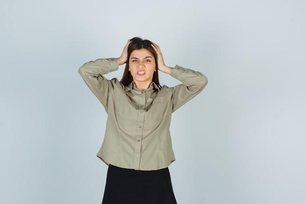 Jonge dame omklemde hoofd met handen in shirt, rok en op zoek verveeld