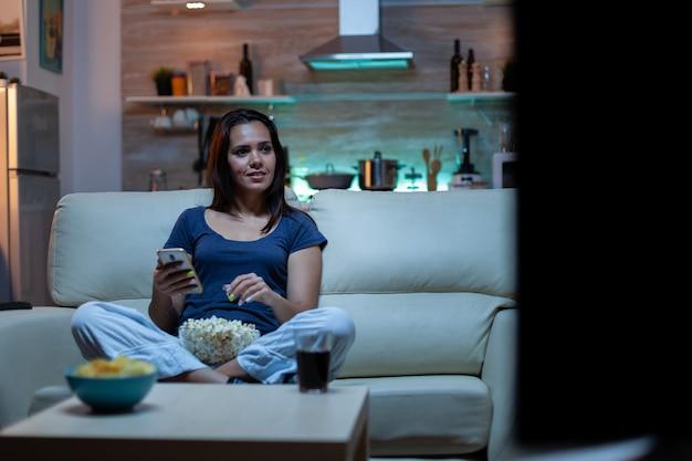 Jonge dame ontspannen 's nachts met behulp van telefoon en tv-kijken zittend op de bank. eenzame geamuseerde gelukkige vrouw lezen, schrijven, zoeken, browsen op smartphone lachen amusant met behulp van technologie internet
