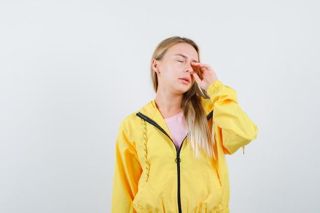 Jonge dame oog wrijven in t-shirt, jasje en slaperig op zoek