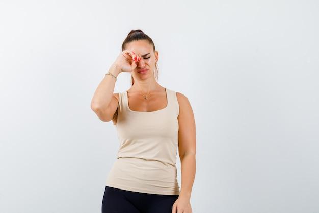 Jonge dame oog wrijven terwijl huilen in tanktop en op zoek depressief, vooraanzicht.