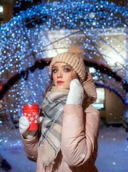 Jonge dame op de achtergrond van bokeh van kerstslingers. kerst portret van een mooi meisje. portret van een meisje op een winternacht met een kopje koffie in haar handen.
