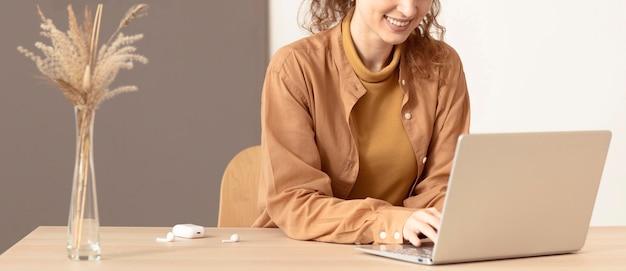 Jonge dame op haar werkruimte met behulp van laptop