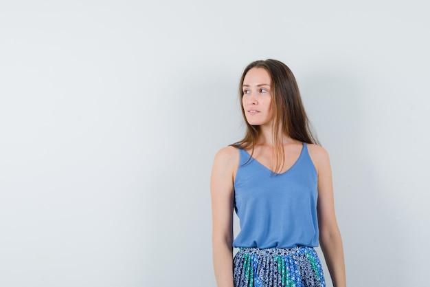 Jonge dame opzij kijken in blouse, rok, vooraanzicht. ruimte voor tekst