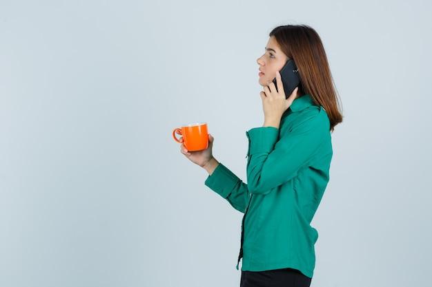 Jonge dame oranje kopje thee houden, praten over de mobiele telefoon in shirt en op zoek attent, vooraanzicht.