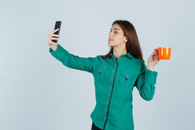 Jonge dame oranje kopje thee houden, selfie met mobiele telefoon in shirt nemen en op zoek naar zelfverzekerd, vooraanzicht.