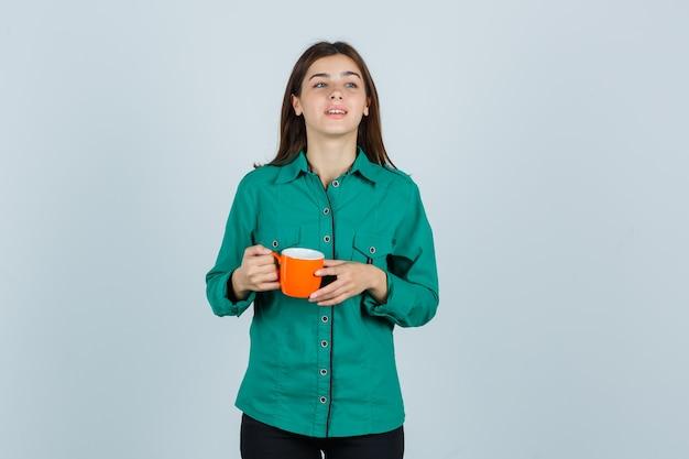 Jonge dame oranje kopje thee in overhemd houden en op zoek vrolijk, vooraanzicht.
