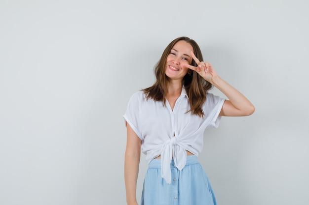Jonge dame overwinning gebaar in blouse en rok tonen en vrolijk kijken