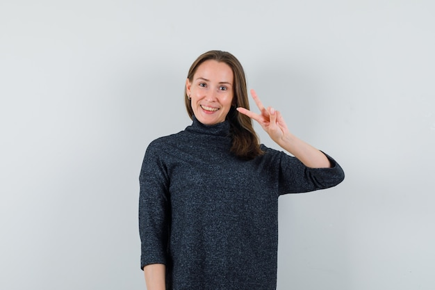 Jonge dame overwinning gebaar in casual shirt tonen en op zoek blij
