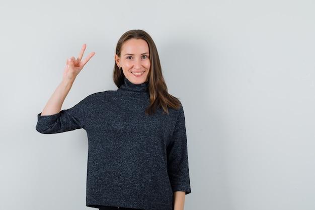 Jonge dame overwinning gebaar in overhemd tonen en op zoek gelukkig