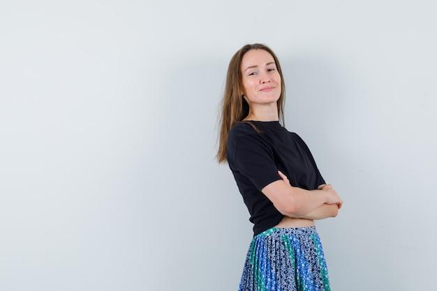 Jonge dame permanent met gekruiste armen in blouse, rok en trots op zoek