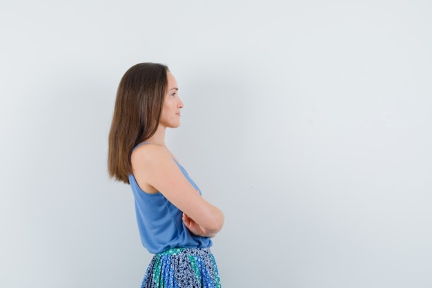 Jonge dame permanent met gekruiste armen in blouse, rok.