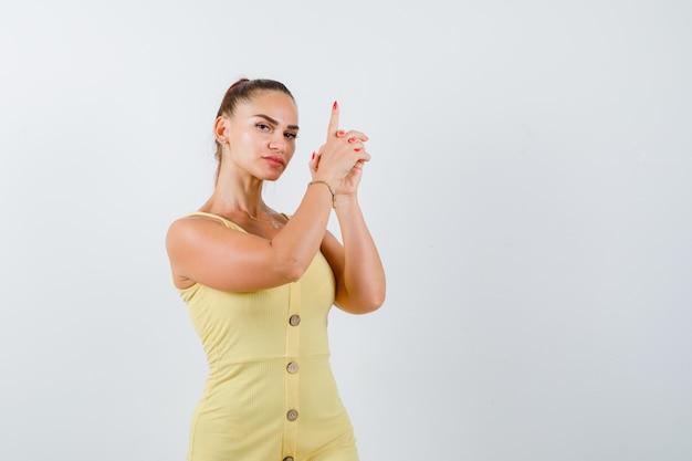 Jonge dame pistool gebaar in gele jurk tonen en op zoek verstandig, vooraanzicht.