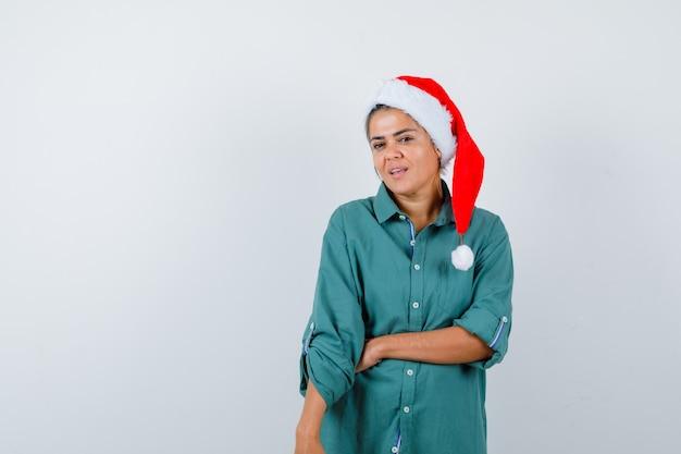 Jonge dame poseren in kerstmuts, shirt en voorzichtig kijken, vooraanzicht.