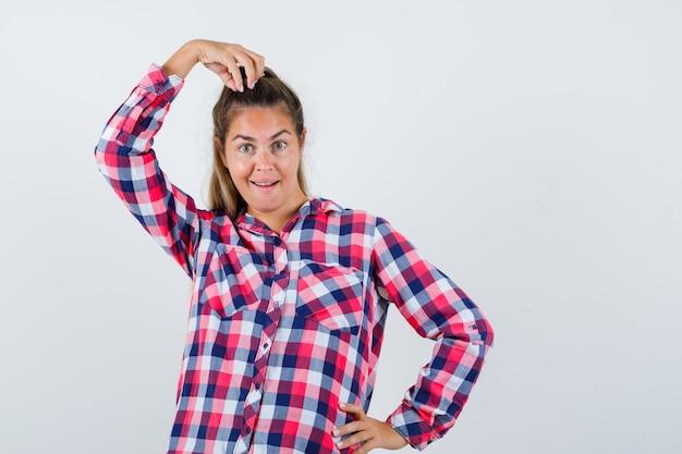 Jonge dame poseren met de hand op het hoofd in geruit overhemd en ziet er grappig uit. vooraanzicht.