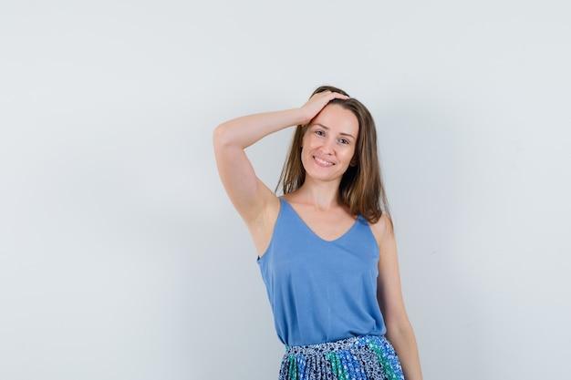 Jonge dame poseren met de hand op het hoofd in hemd, rok en ziet er schattig uit. vooraanzicht.