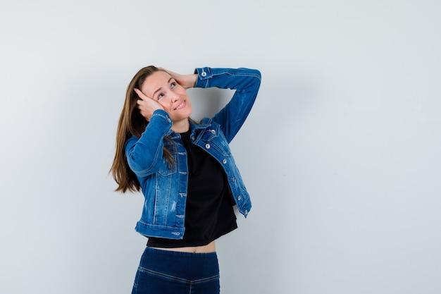 Jonge dame poseren met de handen op het hoofd in blousejeans en ziet er dromerig uit. vooraanzicht.