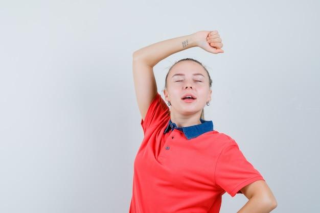 Jonge dame poseren terwijl het opheffen van de arm in een t-shirt en er ontspannen uitziet