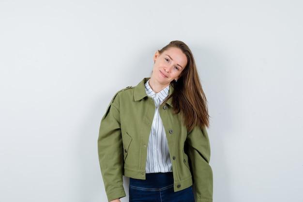 Jonge dame poseren terwijl ze in shirt, jas staat en er prachtig uitziet, vooraanzicht.