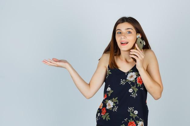 Jonge dame praat op mobiele telefoon, spreidt palm opzij in blouse en kijkt verbaasd, vooraanzicht.