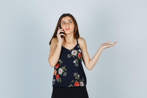 Jonge dame praten op mobiele telefoon in blouse, rok en op zoek geen idee, vooraanzicht.