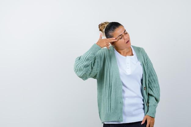 Jonge dame schiet zichzelf neer met handpistool in t-shirt, jas en ziet er hopeloos uit