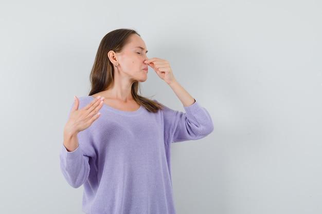 Jonge dame snijdt neus als gevolg van slechte geur in casual shirt en walgt op zoek. vooraanzicht.