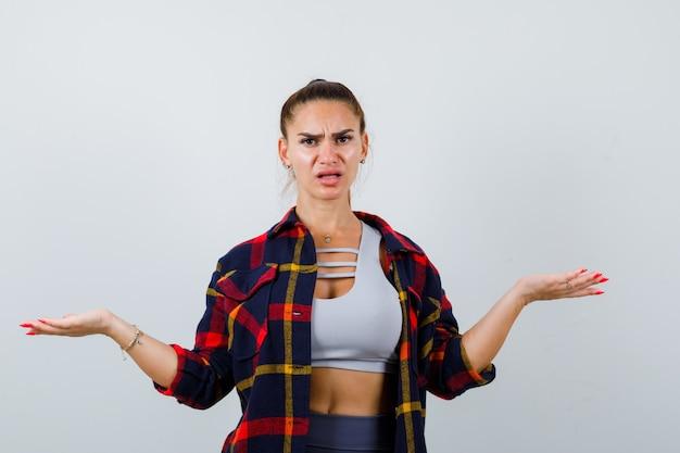 Jonge dame spreidt armen wijd in top, geruit hemd en ziet er serieus uit. vooraanzicht.