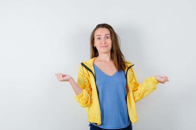 Jonge dame spreidt gebalde vuisten in t-shirt, jas en ziet er vrolijk uit