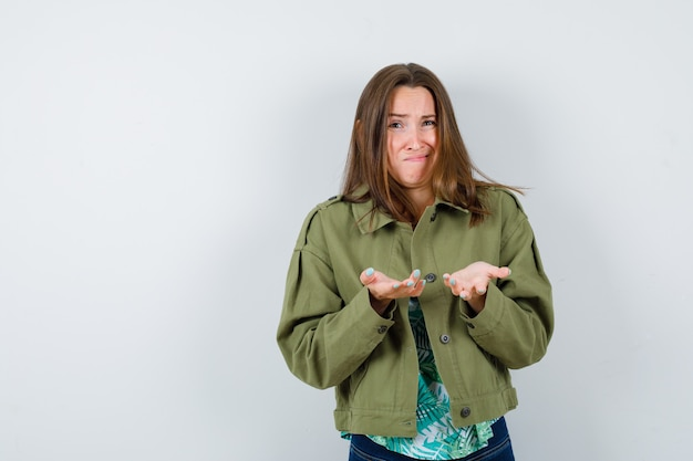 Jonge dame spreidt handpalmen in een onwetend gebaar in blouse, jas en aarzelend, vooraanzicht.