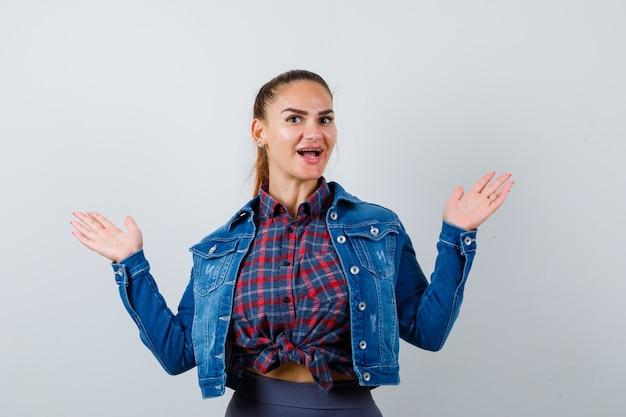 Jonge dame spreidt handpalmen opzij in geruit hemd, spijkerjasje en ziet er vrolijk uit, vooraanzicht.