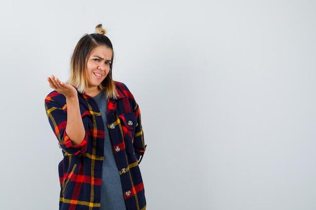 Jonge dame spreidt palm in casual geruit overhemd en kijkt ontevreden, vooraanzicht.