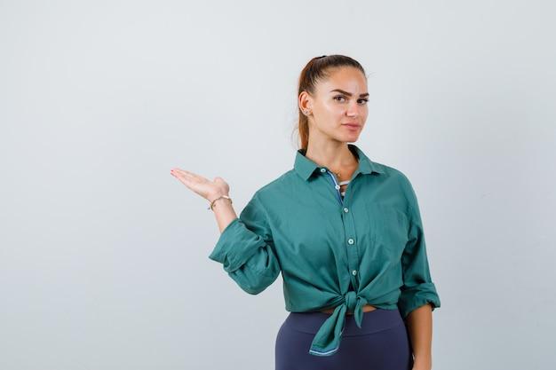 Jonge dame spreidt palm opzij in groen shirt en ziet er zelfverzekerd uit. vooraanzicht.