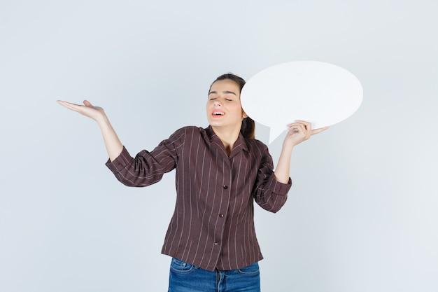 Jonge dame spreidt palm uit, houdt papieren poster in shirt, spijkerbroek en ziet er gelukkig uit, vooraanzicht.